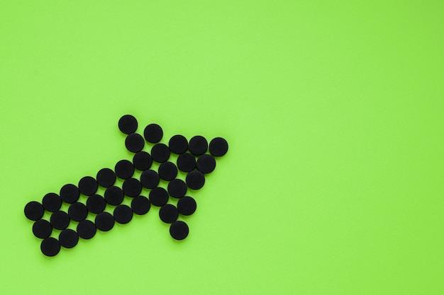 Charbon actif médical sous la forme d'une flèche sur fond vert. vue de dessus, espace copie.