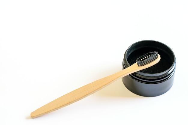 Charbon actif naturel et brosse à dents de bambou sur blanc