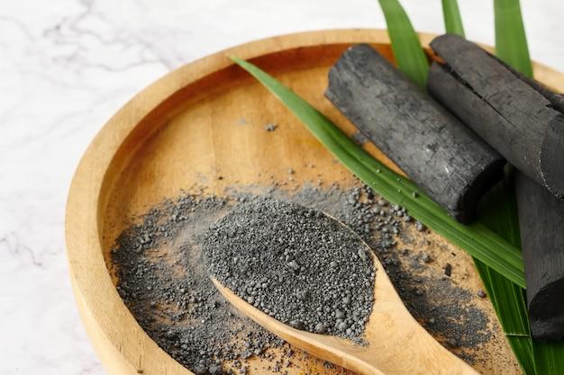 Charbon de bambou et poudre sur table en marbre.