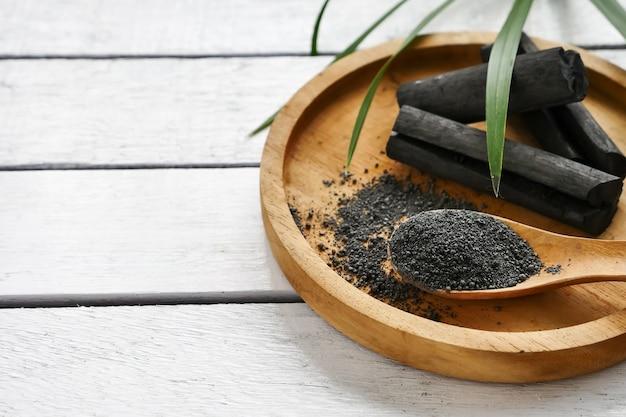 Charbon de bois de bambou et de la poudre sur la table en bois.