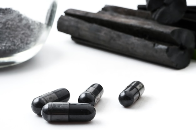 Charbon de bois (charbon actif) en capsules sur fond blanc