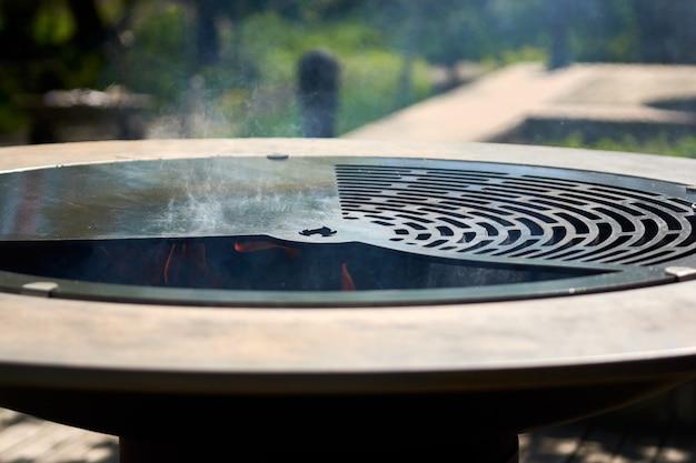Charbon de bois flamboyant dans la fosse de gril de bouilloire avec la grille de fonte. table de cuisson ronde. barbecue chaud avec grille en acier inoxydable sur les aliments de cuisson prêts à griller dans l'arrière-cour. grill avec des flammes à l'intérieur.