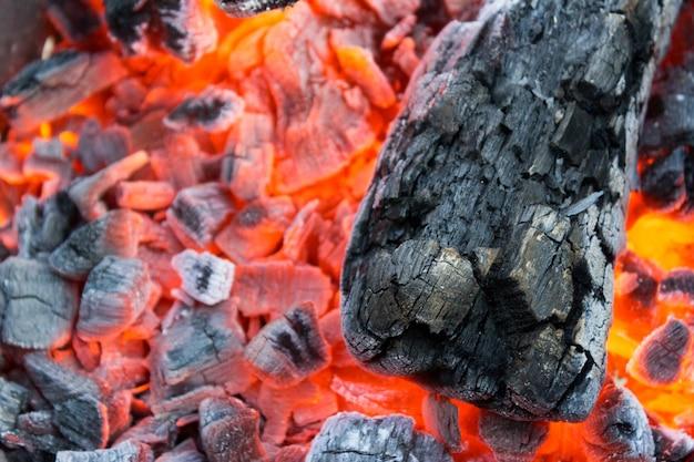 Le charbon de bois qui couve dans un gros plan de barbecue