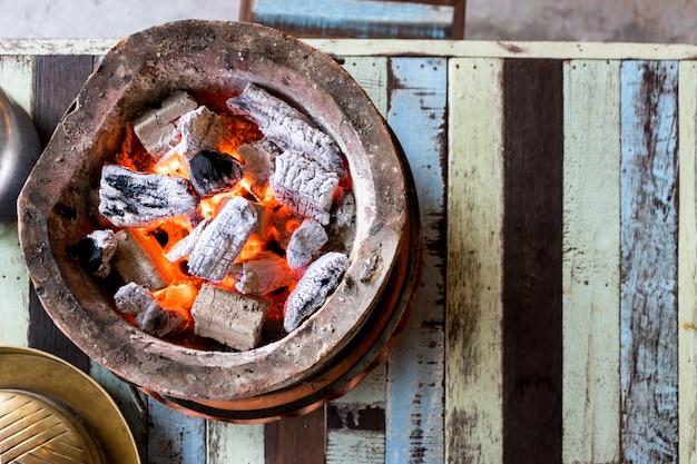 Charbon brûlant avec flamme dans le poêle sur la table
