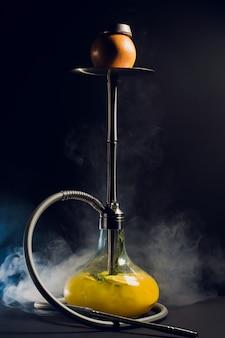 Charbons ardents de narguilé sur bol à chicha avec fond noir. shisha orientale élégante