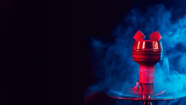 Charbons ardents pour narguilé chicha dans un bol en métal avec de la fumée