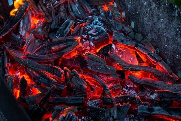Charbons brûlants. charbon de bois en décomposition. texture de braises agrandi. brûler du charbon de bois en arrière-plan.