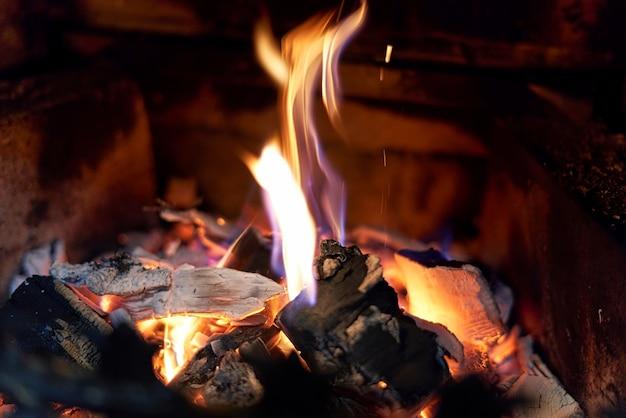 Charbons noirs brûlants et feu élevé dans la cheminée