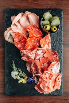 Charcuterie sur plaque de pierre avec prosciutto, bacon, salami et saucisses.