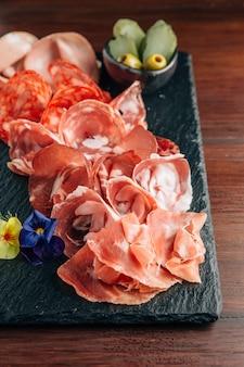 Charcuterie sur plaque de pierre avec prosciutto, bacon, salami et saucisses