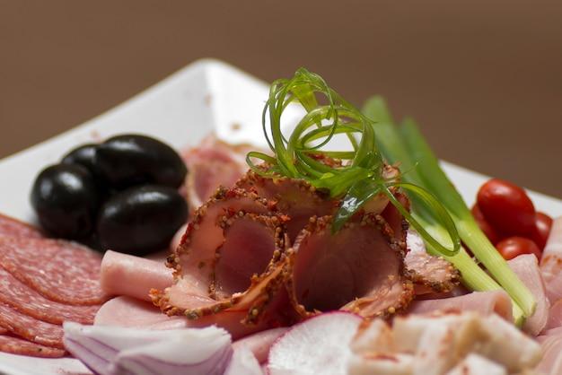 Charcuterie sur plateau - différents types de jambon, bacon, salami, tomates, oignons, feuilles vertes, olives