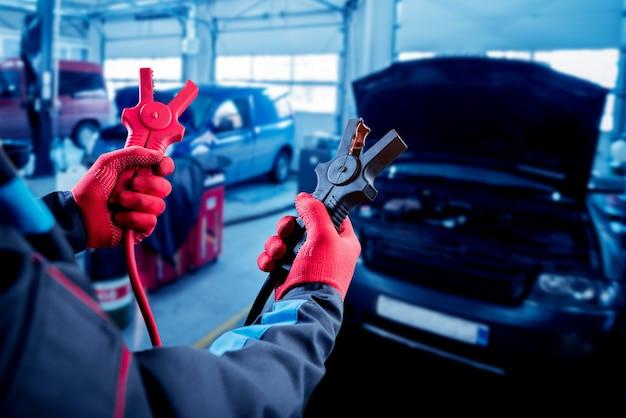 Charge de l'accumulateur. mains et terminaux. réparation automobile.