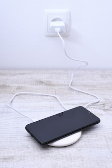 Charge de téléphone portable sur un chargeur sans fil, concept d'équipement moderne