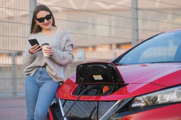 Charge de voiture électrique dans la rue. batteries écologiques connectées et en charge. fille utilise une boisson au café tout en utilisant un smartphone et une alimentation en attente se connecte à des véhicules électriques pour la charge