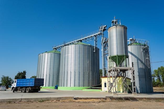 Chargement du grain par camions sur l'élévateur dans des conteneurs métalliques.