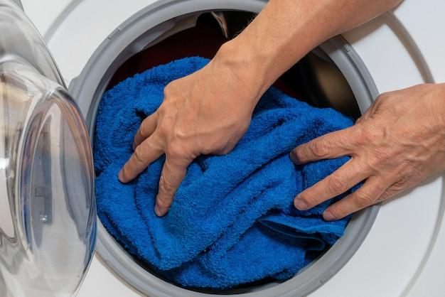 Chargement du linge de lit dans une machine à laver domestique.