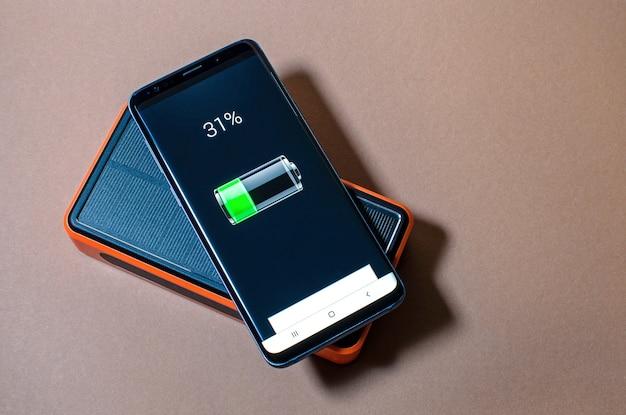 Chargement du smartphone avec bloc d'alimentation solaire orange, niveau de charge.