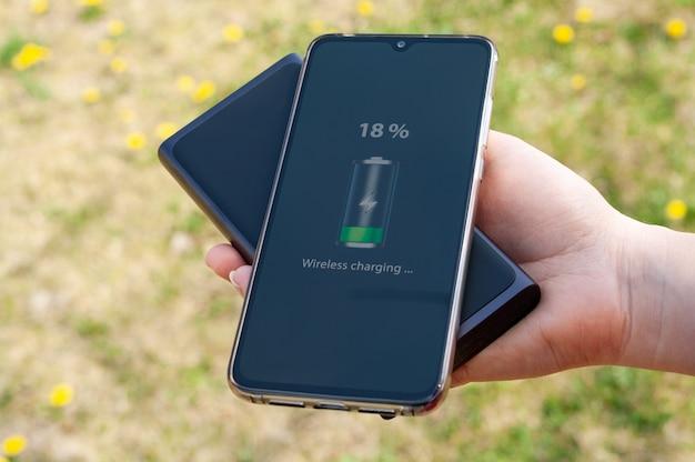 Chargement du smartphone à partir d'une banque d'alimentation à induction dans la main de la femme