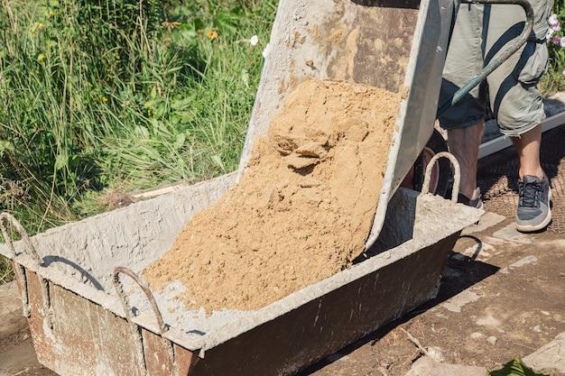 Chargement de sable dans un mélange de ciment pour couler une allée de jardin, travaux de construction sur un terrain de jardin