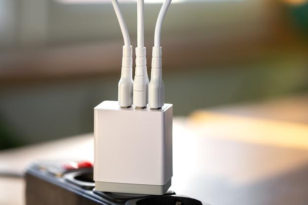Chargement usb blanc pour gadgets sur un arrière-plan flou de la pièce en gros plan
