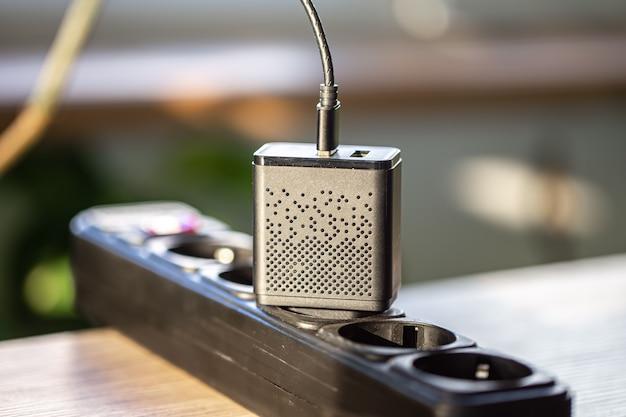 Chargement usb pour les gadgets sur un arrière-plan flou de la pièce en gros plan