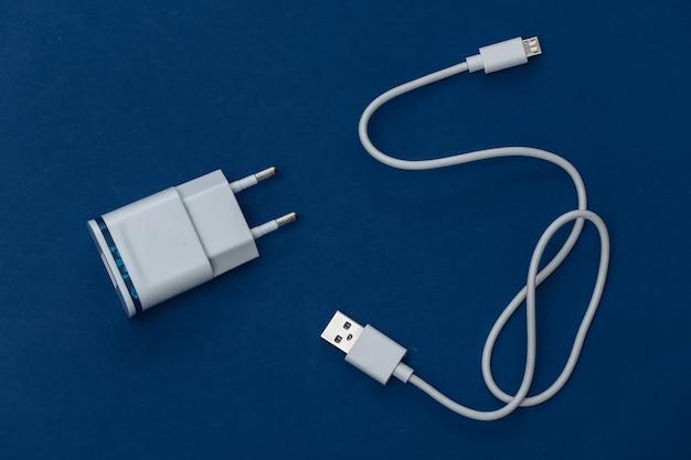 Chargeur avec câble sur fond bleu classique. couleur 2020. vue de dessus
