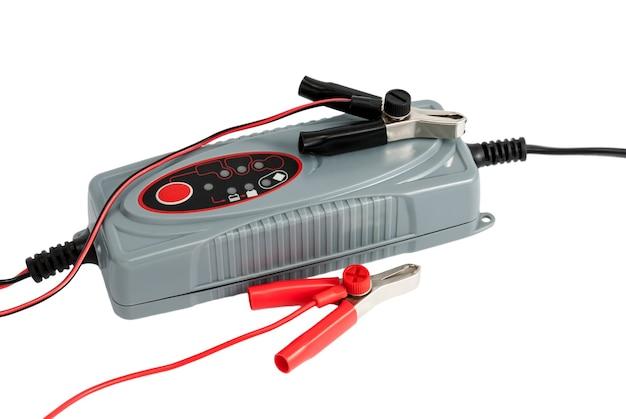 Chargeur électronique moderne pour batterie de voiture avec pinces et câbles de démarrage isolés sur fond blanc