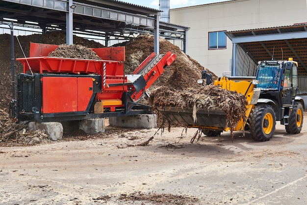 Le chargeur de godet charge l'écorce de bois dans une déchiqueteuse d'arbres industrielle dans une industrie du bois