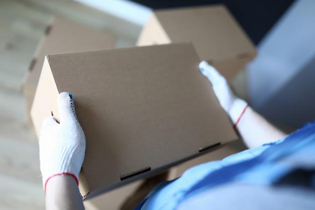 Chargeur de gros plan dans des gants détient une boîte en carton