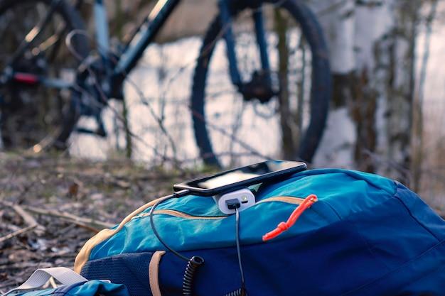 Un chargeur portable charge le smartphone. banque d'alimentation avec câble sur fond de bois et de vélo.