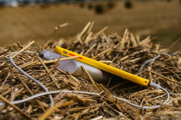 Le chargeur portable charge un smartphone à l'extérieur dans un champ sur fond de foin.