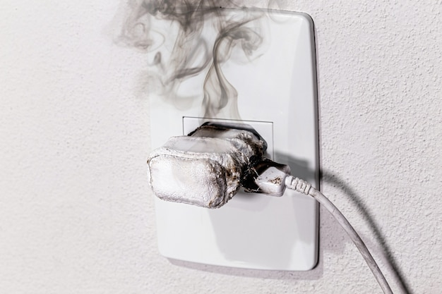 Chargeur de téléphone portable en feu, court-circuit dans la prise