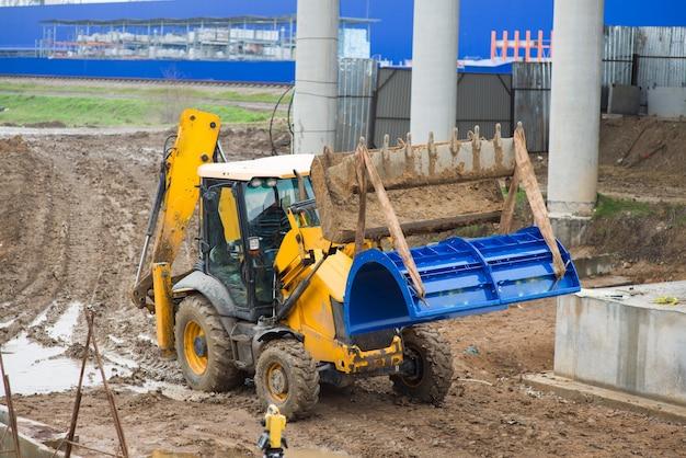 Le chargeur de tracteur de construction déplace une partie du coffrage de colonne de pont