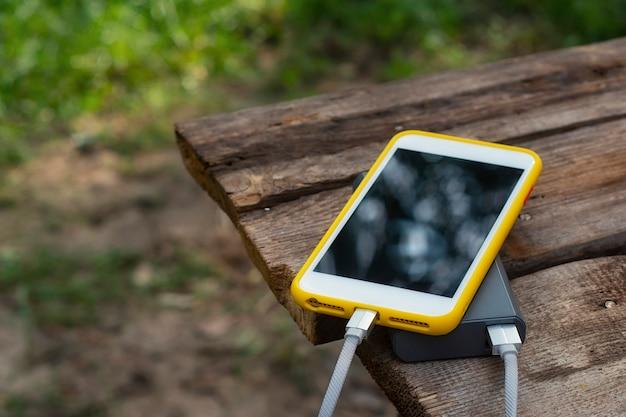 Chargeur de voyage portable. power bank charge un smartphone sur une table en bois, au fond de la nature. concept sur le thème du tourisme.