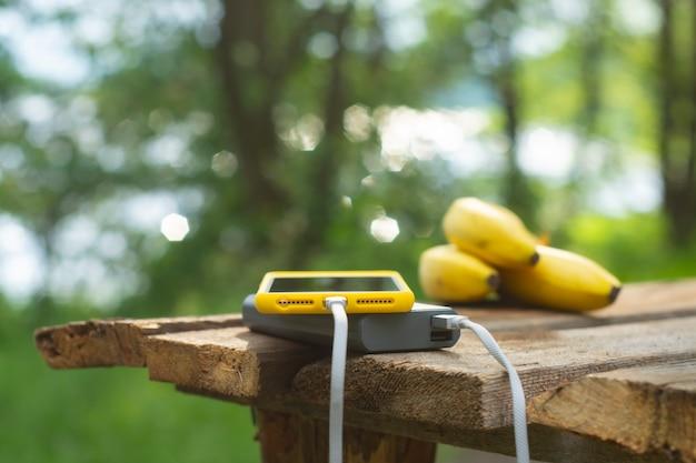 Chargeur de voyage portable. power bank charge un smartphone sur une table en bois avec des bananes, sur fond de nature. concept sur le thème du tourisme.