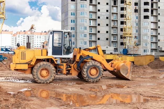 Chargeuse sur pneus lourde avec un godet sur un chantier de construction. equipements pour les terrassements, le transport et le chargement de matériaux en vrac - terre, sable, pierre concassée.