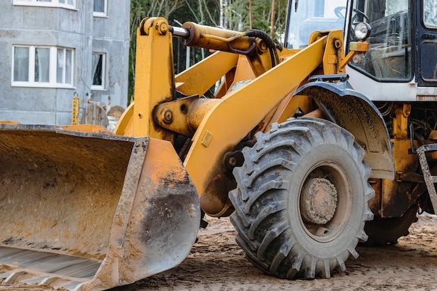 Chargeuse sur pneus lourde avec un godet sur un chantier de construction. equipements pour les travaux de terrassement, le transport et le chargement de matériaux en vrac - terre, sable, pierre concassée.