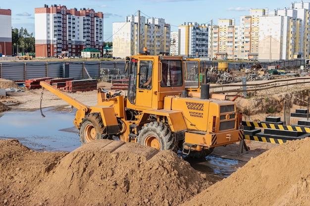 Chargeuse sur pneus puissante pour le transport de marchandises encombrantes sur le chantier de construction d'un quartier résidentiel moderne. matériel de construction pour le levage et le déplacement de charges.