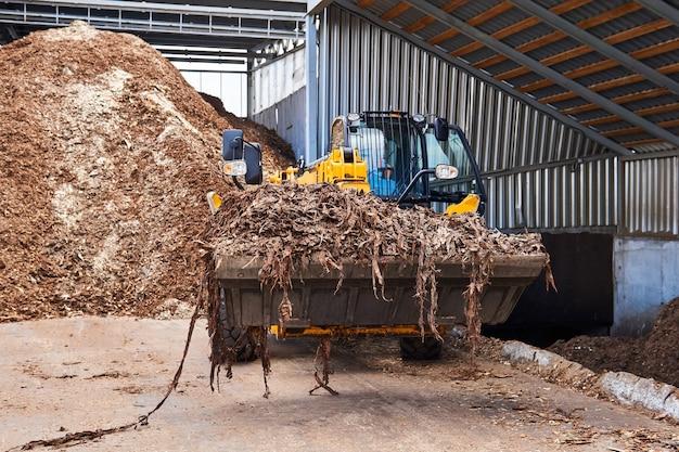 Chargeuse sur pneus avec un seau plein d'écorce dans l'industrie du bois
