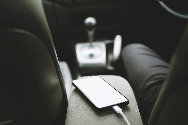 Chargez le téléphone à batterie dans la voiture. placez le téléphone intelligent mobile dans la voiture.
