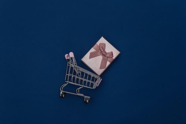 Chariot d'achat avec boîte-cadeau sur fond bleu classique. couleur 2020. vue de dessus.