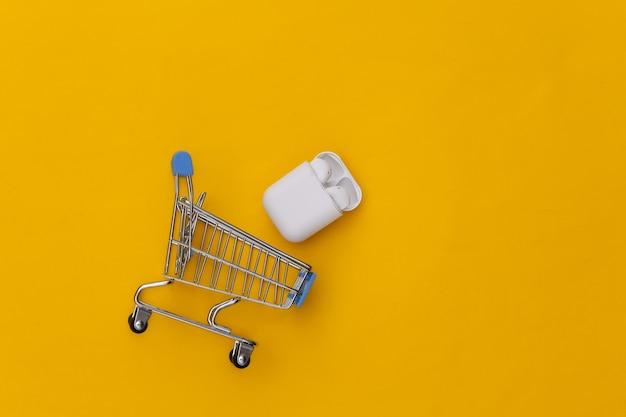 Chariot d'achat et écouteurs sans fil modernes avec étui de chargement sur fond jaune.