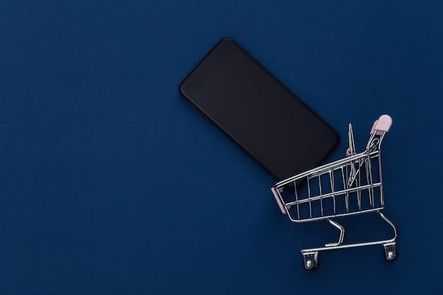 Chariot d'achat avec smartphone sur fond bleu classique. shopping en ligne. couleur 2020. vue de dessus.