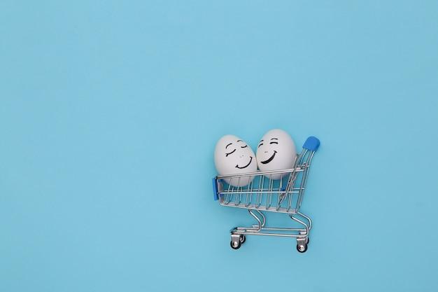 Chariot d'achat avec des visages d'oeufs heureux sur fond bleu