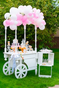 Chariot en bois blanc avec des bonbons décorés de ballons sur l'herbe verte