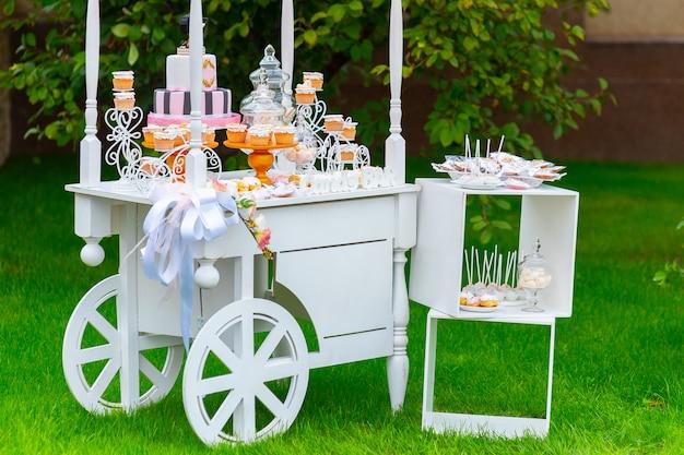 Chariot en bois blanc avec des bonbons sur l'herbe verte dans le jardin