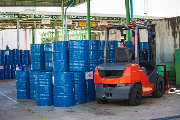 Le chariot élévateur à barils de pétrole se déplace sur le camion de transport.