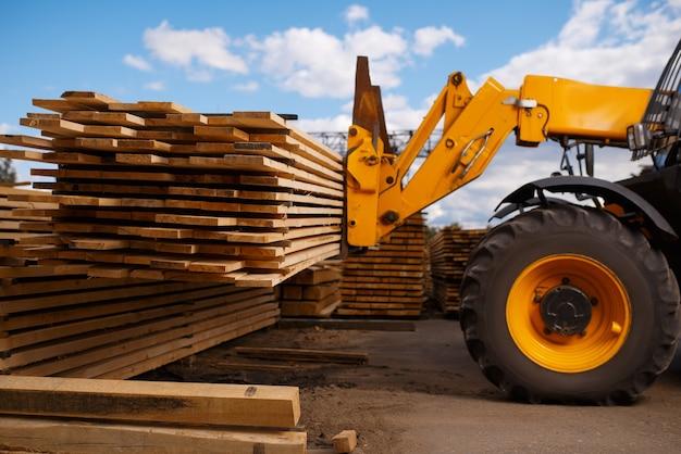 Le chariot élévateur charge les planches dans la cour à bois à l'extérieur. autoloader travaille sur l'entrepôt de la scierie, l'industrie du bois, la menuiserie. traitement du bois en usine, sciage forestier, scierie