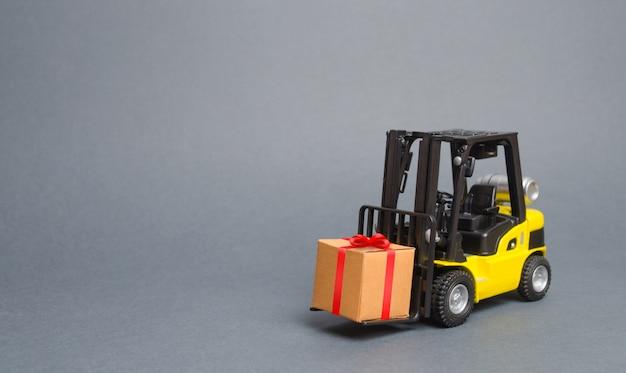 Le chariot élévateur jaune porte un cadeau avec un arc rouge. achat et livraison d'un cadeau. vente au détail