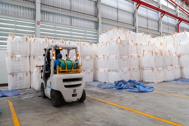 Le chariot élévateur manipule des sacs enorme dans un grand entrepôt.